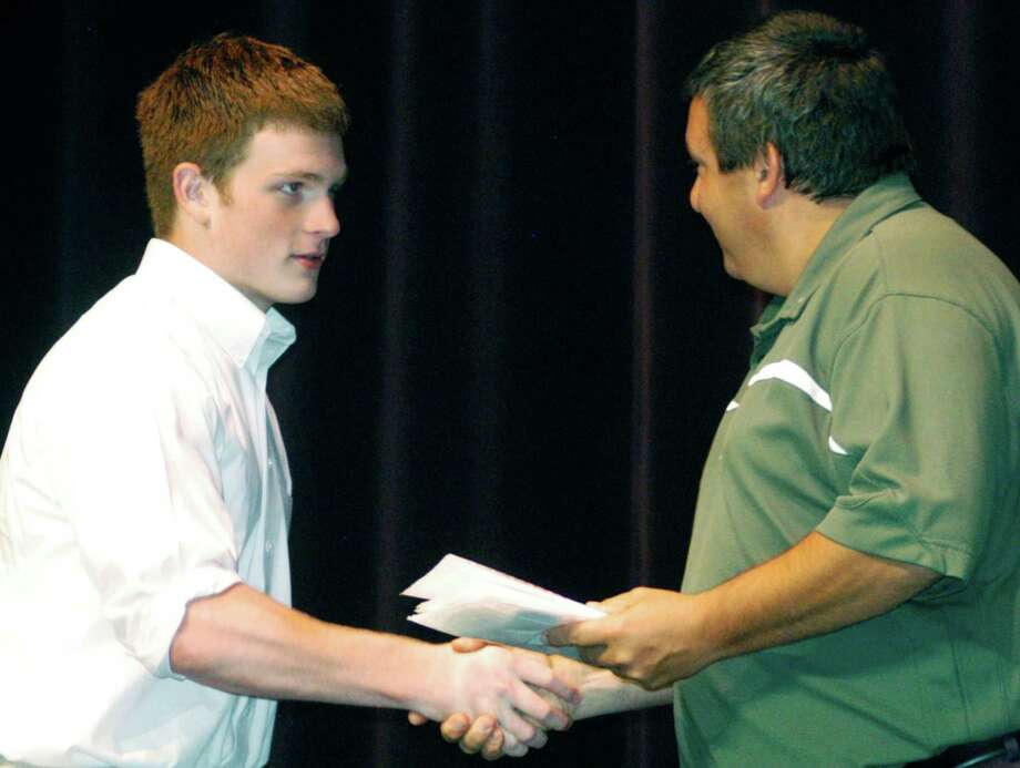 Left, Green Wave boys' lacrosse coach Greg LaCava, at right, congratulates John Phillips during the awards ceremony. Photo: Norm Cummings / Norm Cummings / The News-Times