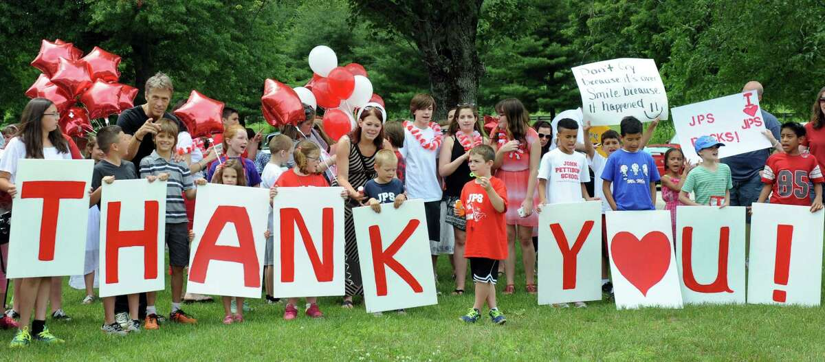 Students and their parents at John Pettibone Elementary School in New Milford hold signs that reflect their feelings on the last day of school Wednesday.
