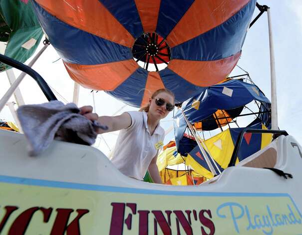 Huck Finn's Playland staff member Samantha Frazer washes off the balloon ride today June 17, 2015 for the official opening tomorrow in Albany, N.Y.      (Skip Dickstein/Times Union) Photo: SKIP DICKSTEIN / 00032078A