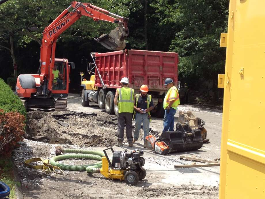 Workers excavate the site where a water main broke near the Cos Cob train station Wednesday. Photo: / Robert Marchant