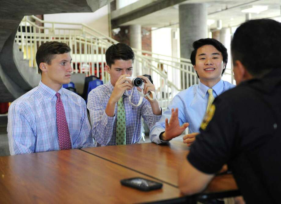 Above and Jack Freiheit, left, Marcus Zabik, center and below, and Naoya Fukuchi interview and photograph School Resource Officer Carlos Franco for their Humans of Greenwich senior project at Greenwich High School Wednesday. Photo: Tyler Sizemore / Hearst Connecticut Media / Greenwich Time