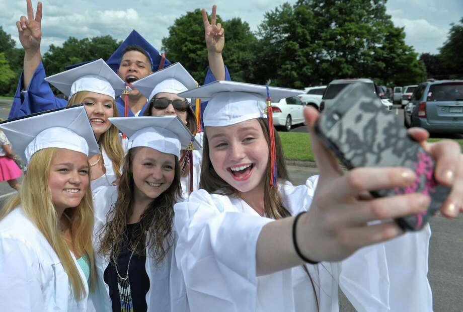 Miranda Brantner, right, snaps a photo of herself with her class mates Kassie Mendes, Austin Nable, Nicole Pacheco, Carly Hewes, Jackie Lesica and Carlos Paulino before they head into the 2015 Danbury High School Commencement Exercises on Wednesday night, June 17, 2015, at Danbury High School, Danbury, Conn. Photo: H John Voorhees III, Hearst Connecticut Media / The News-Times