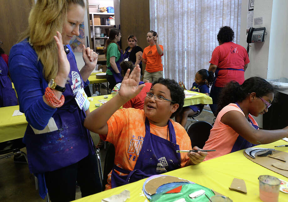 Andrew Holloman, 12, gets a high-five from local artist and instructor Allison Doty, as children continue to stretch their creativity during the afternoon session of Summer Art Ventures Creative Kids Camp 2015 Wednesday at the Art Museum of Southeast Texas. Local artists, assisted by student volunteers, are leading the morning and afternoon art camp, exposing youth to a variety of techniques and styles, ranging from painting to screen printing and painting. While a boon to budding artists, the camp also provides one of the biggest employment opportunities to area artists, according to Christle Feagin, Curator of Education/Programs at the museum. The five-week camp continues through mid-July.  Photo taken Wednesday, June 17, 2015 Kim Brent/The Enterprise Photo: Kim Brent / Beaumont Enterprise
