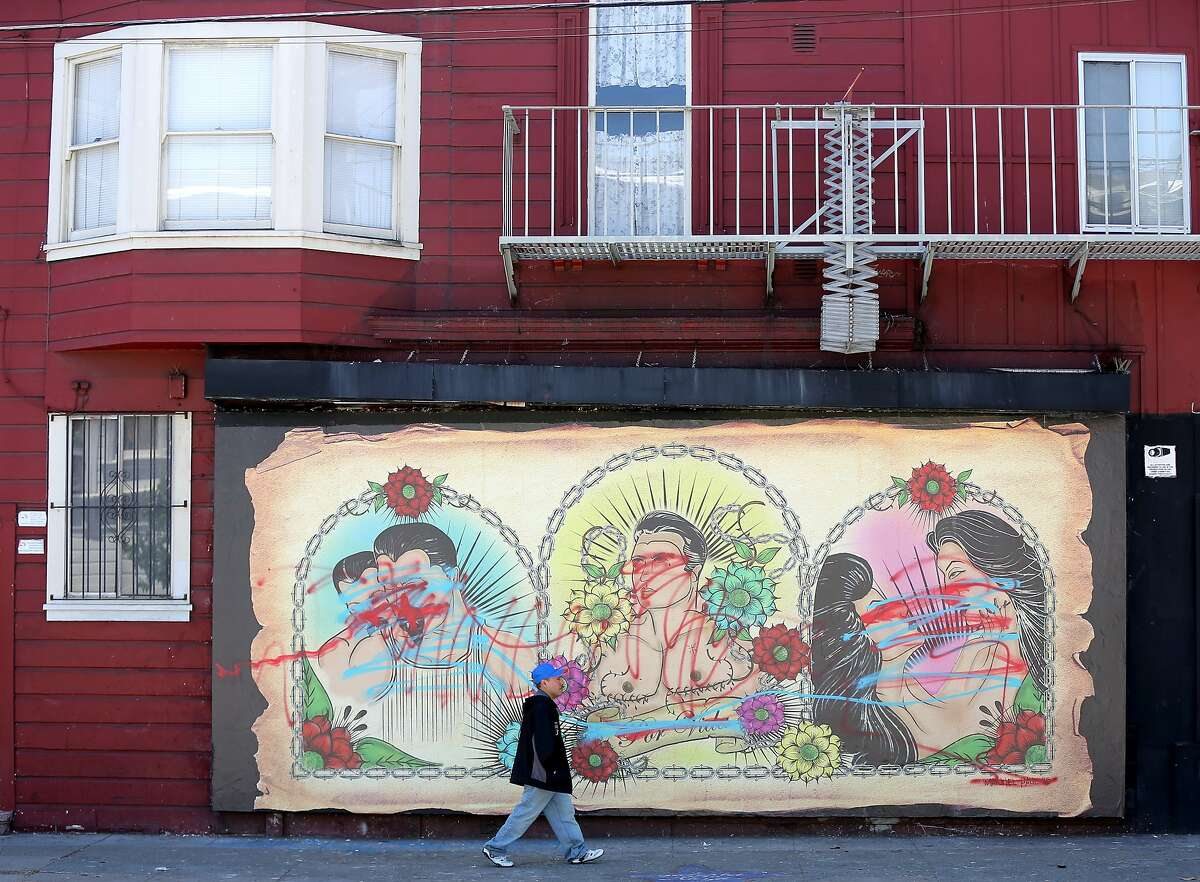 A man passes by a new gay latino mural near the corner of 24th and Bryant streets in the Mission District that was defaced by spray paint in San Francisco, California, on Wednesday, June 17, 2015.