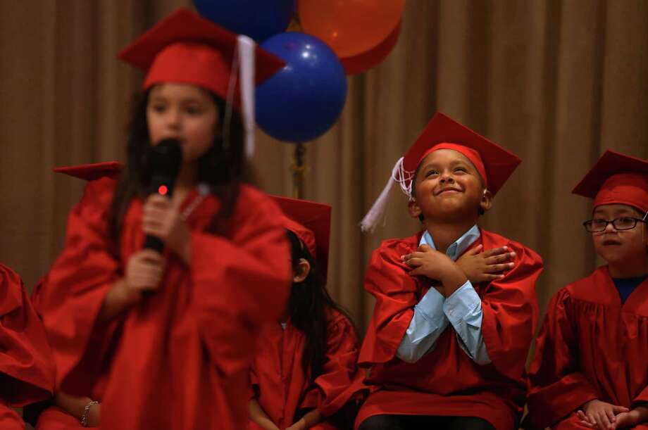 Joe Perez, gives a gesture of approval he learned in school meaning he loves his school and classmates, during the kindergarten graduation ceremony at The Center for Hearing and Speech on Wednesday, June 17, 2015, in Houston. Thirteen local deaf children graduate from the Melinda Webb School at The Center for Hearing and Speech. Photo: Mayra Beltran, Houston Chronicle / © 2015 Houston Chronicle