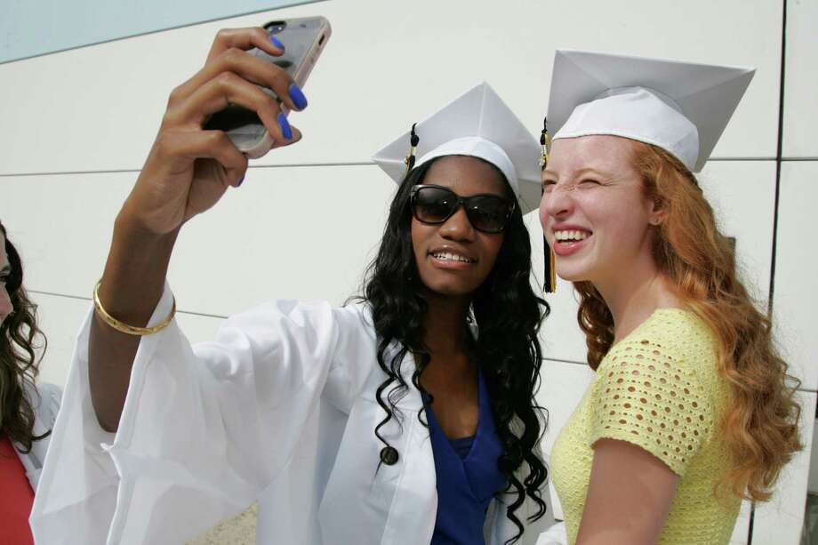 Scheba Derogene and Ali Hardisty, both of Easton, snap an iPhone photo prior to the 2015 Joel Barlow High School commencement ceremony at the William A. O'Neill Center, Western Connecticut State University in Danbury, Conn. on Wednesday, June 17, 2015. Photo: Matthew Brown, For Hearst Connecticut Media / Connecticut Post Freelance