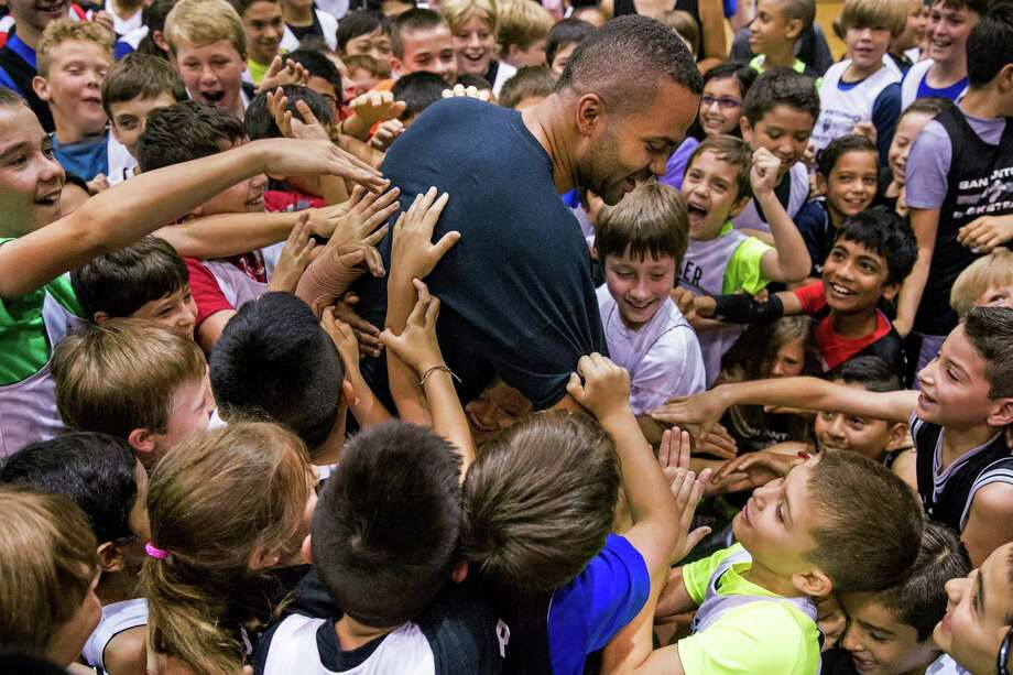 Tony Parker is mobbed by children after hitting a half-court shot during his basketball camp at the George Gervin Youth Center. Photo: Ray Whitehouse / San Antonio Express-News / 2015 San Antonio Express-News