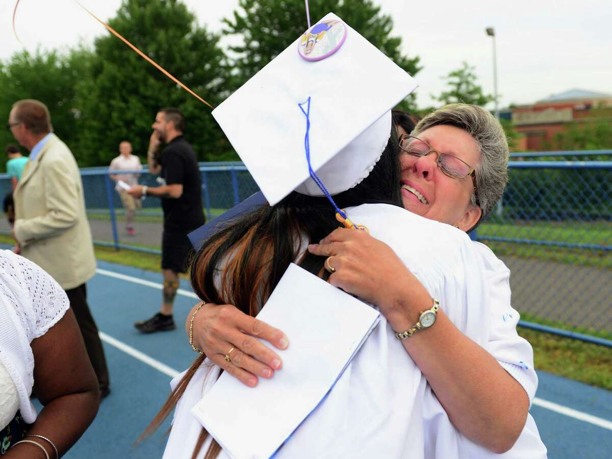 Graduate Grace Mitchell gets a hug from Wendy Poeta-Tisi, of Shelton, aunt of Mitchell's classmate Nina Poeta, after Seymour High School's 128th Annual Commencement in Seymour, Conn., on Wednesday June 17, 2015. Mitchell was best friends with Poeta, who would have graduated today but died after her battle with cancer last year.