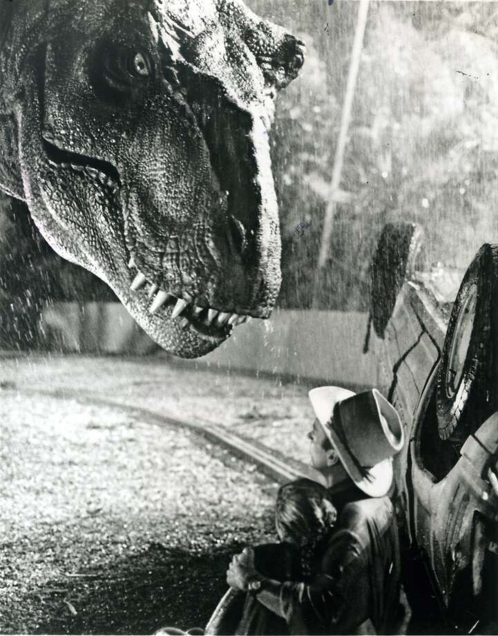"A huge Tyrannosaurus rex stares down at paleontologist Dr. Alan Grant (Sam Neill) who is protecting the teen-age Lex (Ariana Richards), in ""Jurassic Park."" Photo: Universal Pictures"