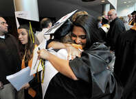 Priya Gada, right, and Bridget Smith embrace following the Academy of Information Technology and Engineering graduation ceremony at Rippowam Middle School in Stamford, Conn., on Wednesday, June 17, 2015.