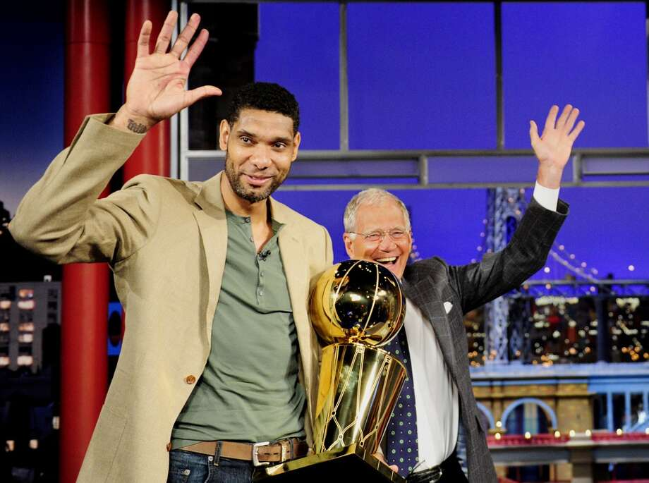 """In this photo provided by CBS, Tim Duncan of the San Antonio Spurs, waves to the audience while holding the Larry O'Brien NBA Championship Trophy on the set of the """"Late Show with David Letterman,"""" Tuesday, June 24, 2014 in New York. At right is the show's host, David Letterman. (AP Photo/CBS, John Paul Filo) MANDATORY CREDIT, NO SALES, NO ARCHIVE, FOR NORTH AMERICAN USE ONLY Photo: Associated Press"""