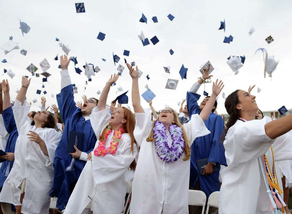 Graduates Elizabeth Buckley, Melanie Albright and Cami Adajian, from left, toss their caps at the end of the Fairfield Ludlowe High School commencement ceremony Wednesday, June 17, 2015.