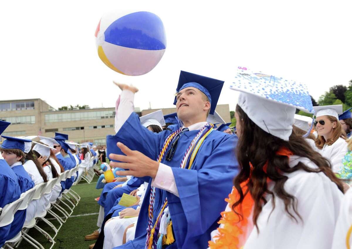 Graduate Nick Warkentin sends a beach ball into the air over his classmates during the Fairfield Ludlowe High School commencement ceremony Wednesday, June 17, 2015 on the school's Taft Field.