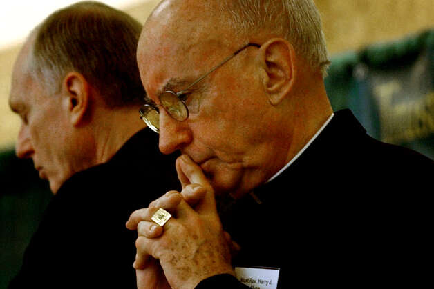 Archbishop Harry J. Flynn of the Archdiocese of Saint Paul and Minneapolis takes part in an opening prayer at the start of a symposium on clergy  sexual misconduct Saturday, March 29, 2003, at Siena College in Loudonville, N.Y. Albany Bishop Howard J. Hubbard is to the left of Flynn. (Michael P. Farrell/Times Union archive) Photo: MICHAEL P. FARRELL / ALBANY TIMES UNION