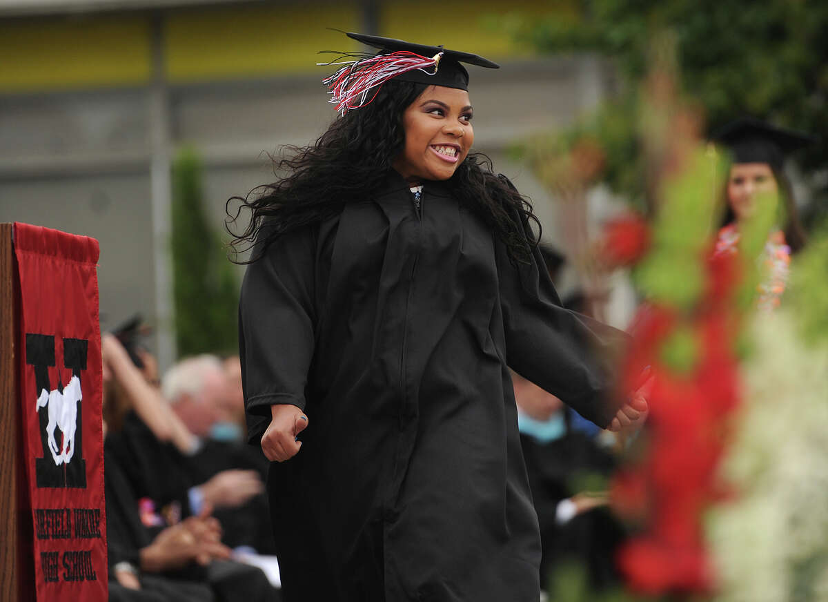 Graduate Breanna Corbin smiles to the crowd as she walks to receive her diploma during Fairfield Warde graduation in Fairfield, Conn. on Wednesday, June 17, 2015.