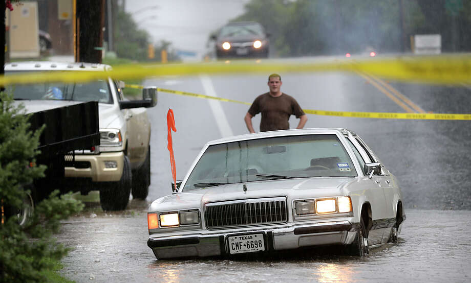 Connor Flynn, out for a run in his neighborhood, stops as he encounters a blocked off road where  a car was washed to the side of the road on McCullough at E. Magnolia on Wednesday June 17, 2015. Photo: Bob Owen, Staff / San Antonio Express-News / ©2015 San Antonio Express-News