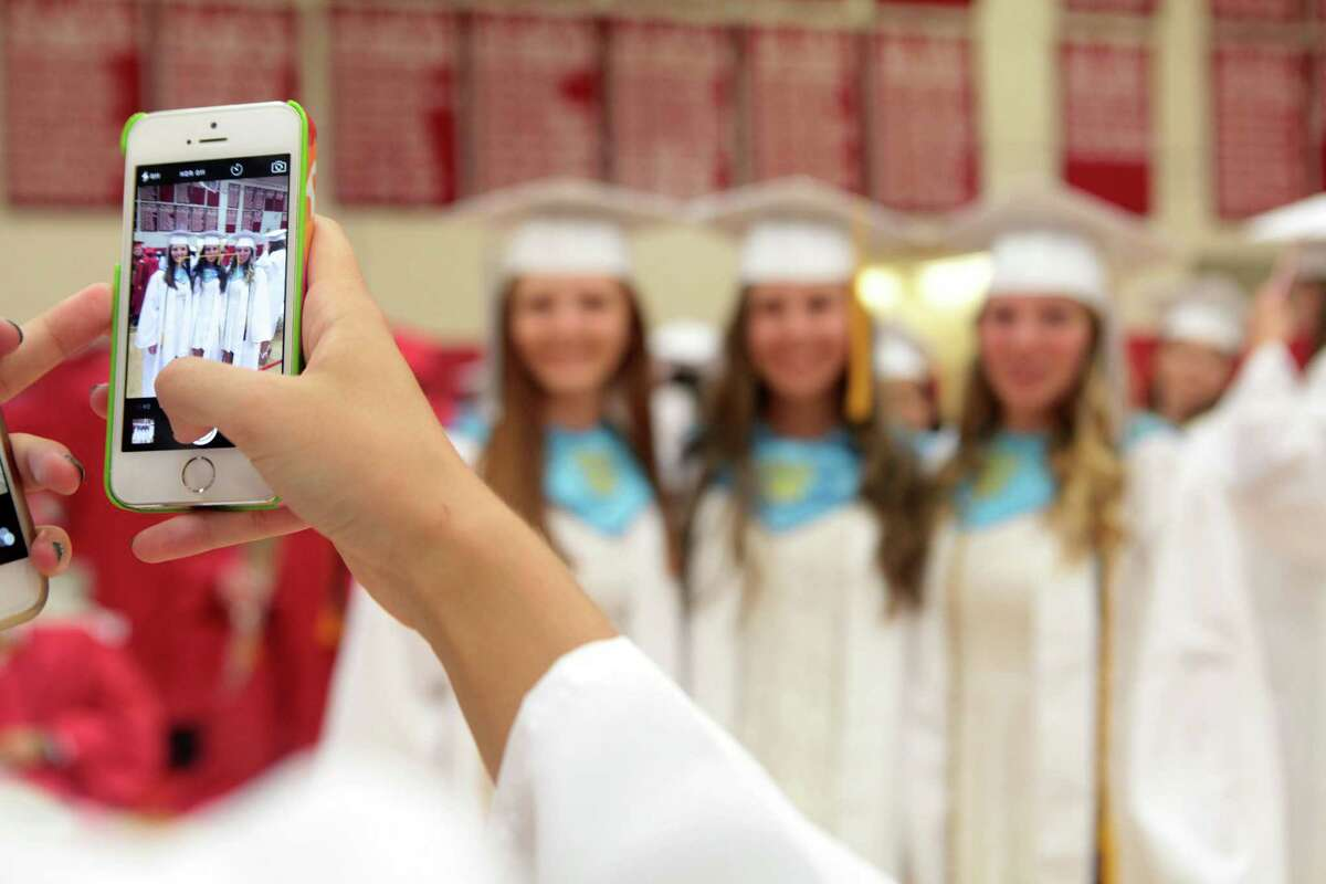 Masuk High School graduates, from left, Julia Scanzillo, Kamilla Borsai, and Taylor Shaw pose before commencement exercises in Monroe, Conn. on Wednesday, June 17, 2015.
