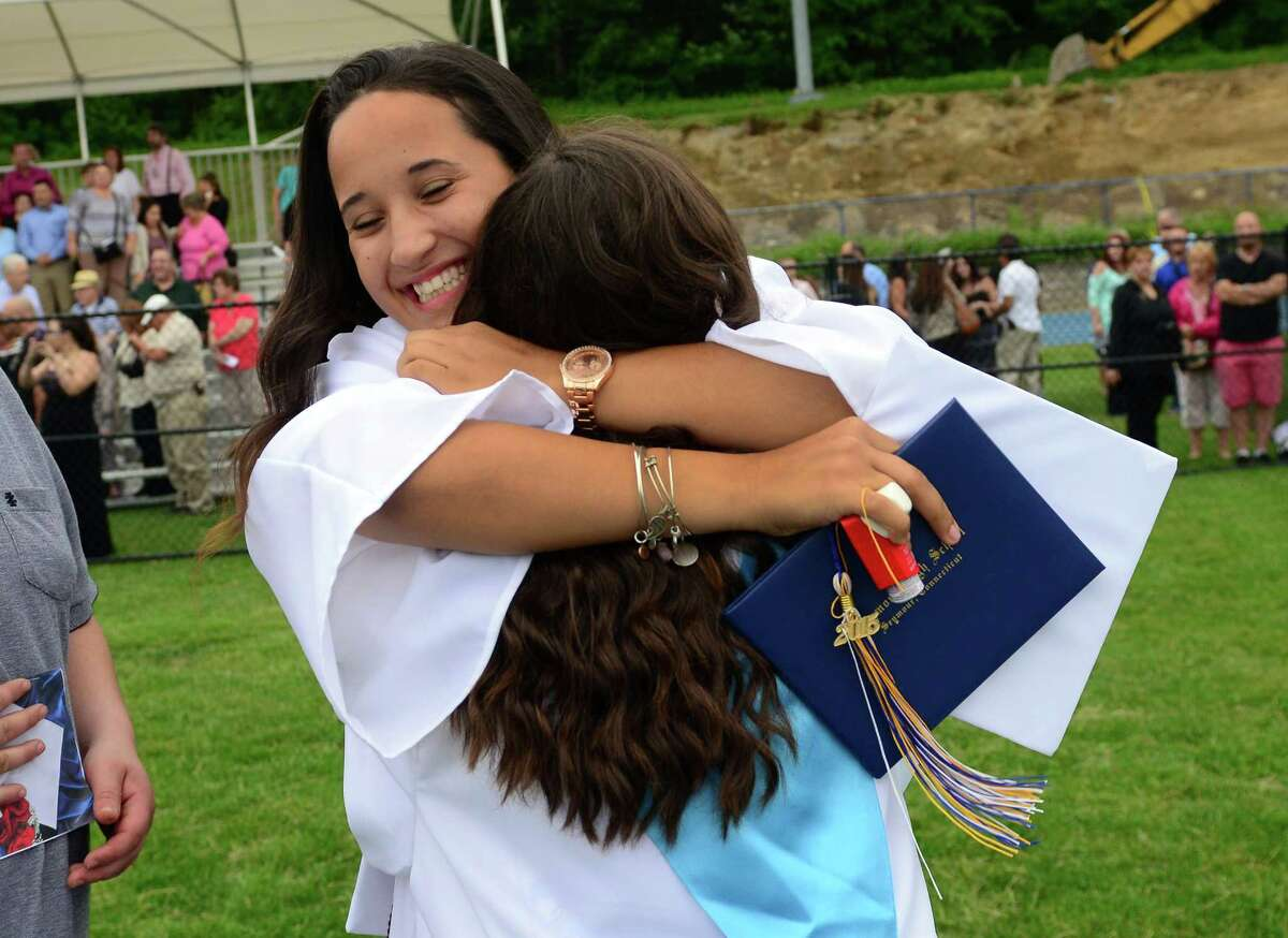Graduate Gaby Torelli, facing camera, gets a hug from classmate Myranda Williams, after Seymour High School's 128th Annual Commencement in Seymour, Conn., on Wednesday June 17, 2015.