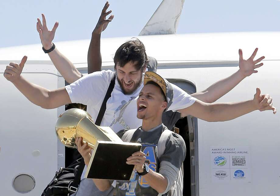 Andrew Bogut, (top) and Stephen Curry depart the plane with the championship trophy in hand, as the Golden State Warriors, the 2015 NBA Champions, landed at Oakland International Airport  in Oakland, Calif., on Wed. June 17, 2015. Photo: Michael Macor, The Chronicle