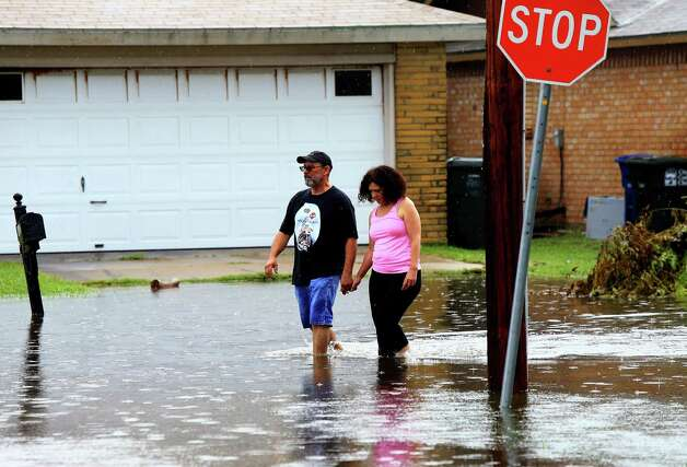 Bobby Mitchell and Sylvia Mitchell walk in flooded waters caused by heavy rains Wednesday, June 17, 2015 on Silver Sands Drive in Corpus Christi, Texas. (Gabe Hernandez/Corpus Christi Caller-Times via AP)  ORG XMIT: TXCOR102 Photo: Gabe Hernandez / Corpus Christi Caller-Times