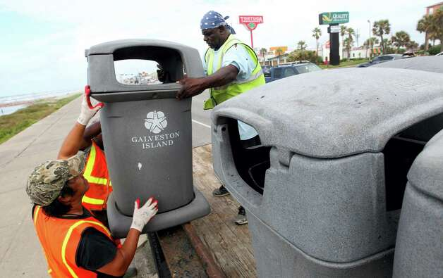 Galveston Island Park Board of Trustees crews removed trash barrels from the seawall Monday June 15, 2015, as they prepare for the tropical disturbance headed toward the Gulf coast, in Galveston, Texas. A low pressure area located over the south central Gulf of Mexico is being monitored by the National Hurricane Center for possible tropical cyclone formation as it moves northwest towards the middle and upper Texas coast. (Jennifer Reynolds/The Galveston County Daily News via AP) ORG XMIT: TXGAL102 Photo: Jennifer Reynolds / The Galveston County Daily News