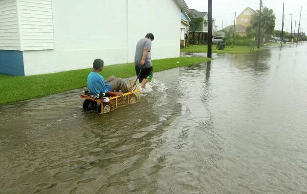 CORRECTS TRANS REF AND CREDIT - Manuel Martinez pulls Jesse McGehee through high water on Saladia Street in Galveston, Texas on Tuesday June 16, 2015. High tides cause by Tropical Storm Bill flooded several low-lying streets. (Jennifer Reynolds/The Galveston County Daily News via AP)  ORG XMIT: TXGAL104 Photo: Jennifer Reynolds / The Galveston County Daily News