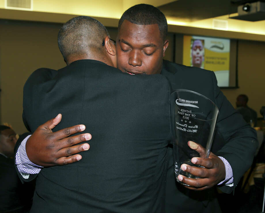 Father of the Year Brian Mills-Bolling (right) gets a hug from his own father Rodney Walters as 100 Black Men of San Antonio presents its Fatherhood Jubilee at St. Phillips College on June 16, 2015. Photo: Photos By Tom Reel / San Antonio Express-News