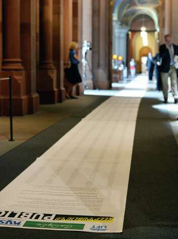 A 60-yard-long NYSUT petition is layer along a hallway outside the governor's office Wednesday, June 17, 2015, at the Capitol in Albany, NY. (John Carl D'Annibale / Times Union) Photo: John Carl D'Annibale / 00032313A