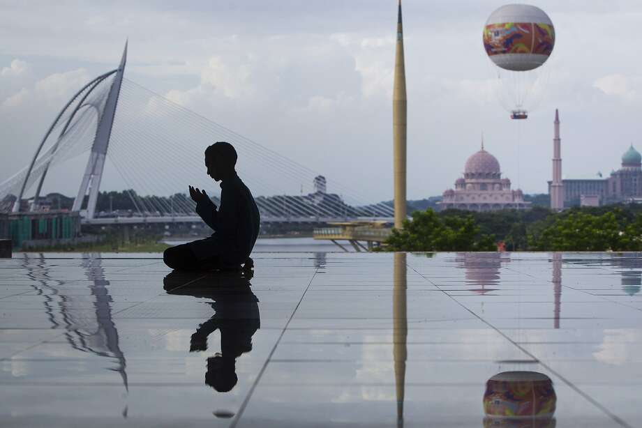 A Malaysian Muslim man is silhouetted as he performs his prayers at a mosque in Putrajaya, Malaysia Wednesday, June 17, 2015. During Ramadhan, Muslims refrain from eating, drinking, smoking and sex from dawn to dusk. Muslims are called to practice more actively the dictates of their faith such as tolerance, patience and an increase in works of charity. Photo: Joshua Paul, Associated Press