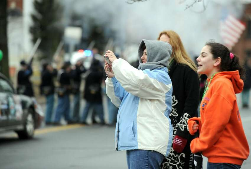 Kathleen Cardamone, with camera, and Christine Cardamone, right, watch the St. Patrick's Day Parade as it winds onto West St. Danbury Sunday afternoon, March 14, 2010.