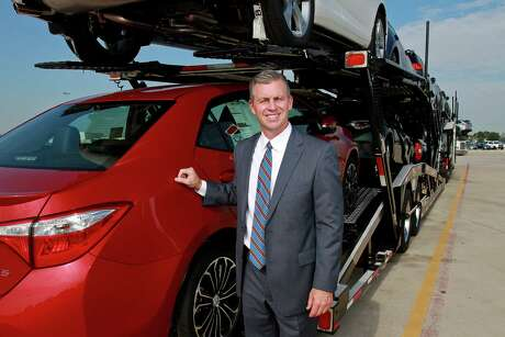 Martin Collins, president of Gulf States Toyota, at their vehicle processing center, with a transport truck of Toyotas that are headed for one of their dealers.