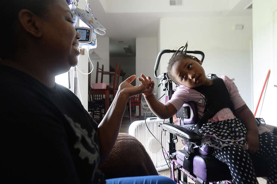 Three-year-old David Chatman plays with her home health care nurse Demeatrice Fisher at her family's Port Acres home Tuesday. David was born with Dravet Syndrome, a rare form of epilepsy that affects only several hundred people worldwide.  Photo taken Tuesday, June 16, 2015  Kim Brent/The Enterprise Photo: Kim Brent / Beaumont Enterprise