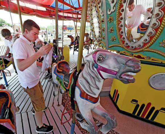 Staff member Nik Faresta puts some shine on the saddle of one of the carousel horses at Huck Finn's Playland  today June 17, 2015 for the official opening tomorrow in Albany, N.Y.      (Skip Dickstein/Times Union) Photo: SKIP DICKSTEIN / 00032078A