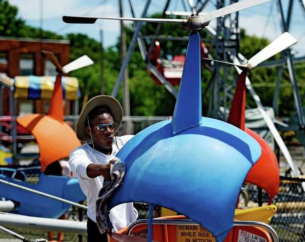 Staff member Najja O'Connor cleans dust from one of the helicopter rides cars at  Huck Finn's Playland today June 17, 2015 in preparation for the official opening tomorrow in Albany, N.Y.      (Skip Dickstein/Times Union) Photo: SKIP DICKSTEIN / 00032078A