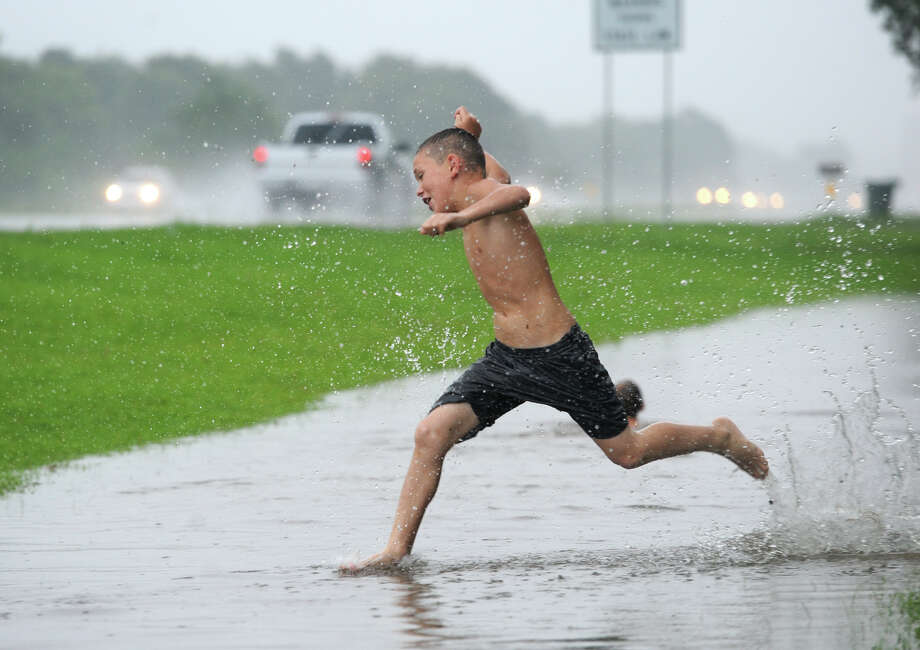 Trent Watts, 10, plays in water along U.S. 90 near Keith Road during Wednesday's heavy rains. Tropical Storm trekked through Texas Wednesday dumping several inches of rain in Southeast Texas.  Photo taken Wednesday, June 17, 2016  Guiseppe Barranco/The Enterprise Photo: Guiseppe Barranco, Photo Editor