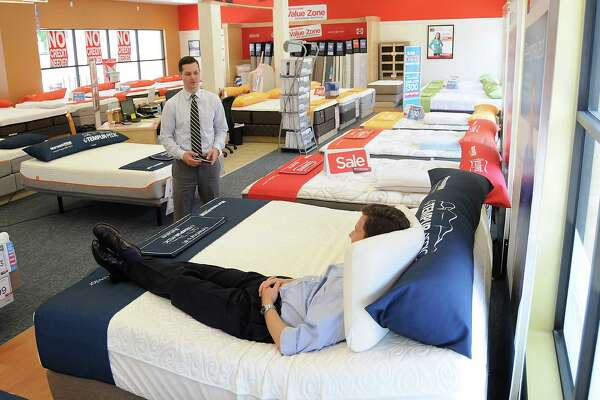 Area manager David Bucklew adjusts a bed for a customer at the Mattress Firm on W. Gray Monday May 01, 2015.(Dave Rossman photo)