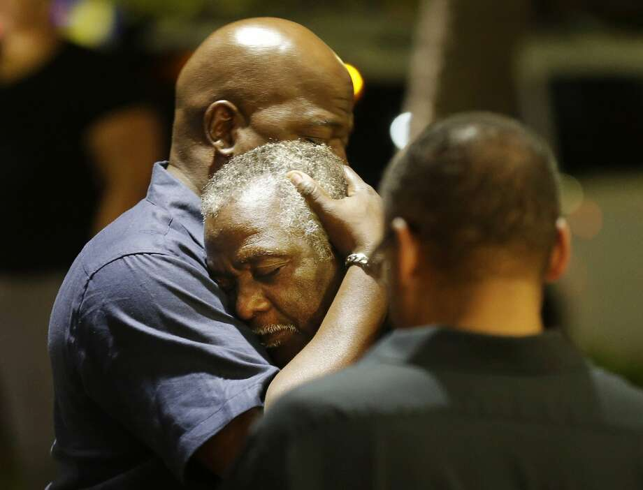 Worshippers embrace following a group prayer in Charleston, S.C. Photo: David Goldman, Associated Press