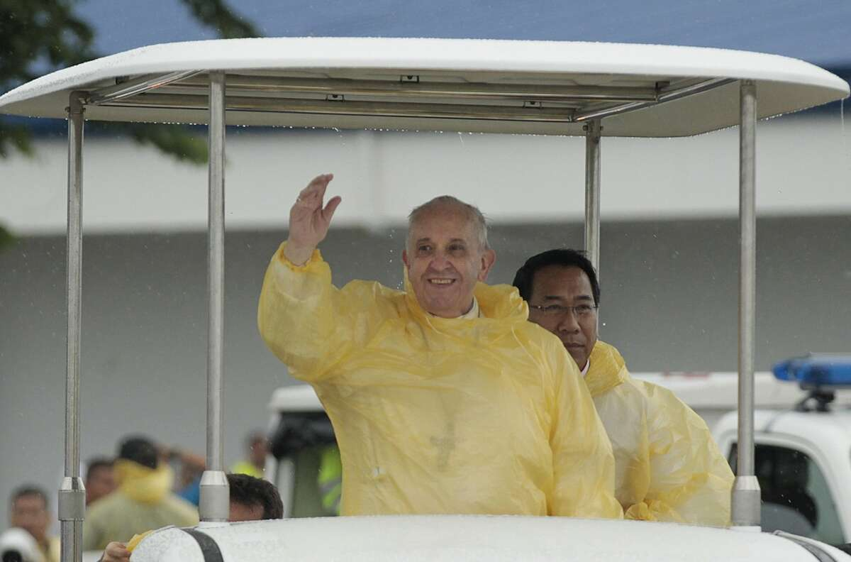 FILE - In this Jan. 17, 2015 file photo, Pope Francis waves to the faithful on his arrival in Tacloban, Philippines as rain drips from the roof of his vehicle. From Galileo to genetics, the Roman Catholic Church has danced with science, sometimes in a high-tension tango but more often in a supportive waltz. Pope Francis is about to introduce a new twist: global warming. The field of genetics was started by a Catholic cleric, Gregor Mendel. Entire aspects of astronomy, including the genesis of the Big Bang theory, began with Catholic clerics. While some religions reject evolution, Catholicism has said for 65 years that it fits with the story of creation. (AP Photo/Wally Santana, File)