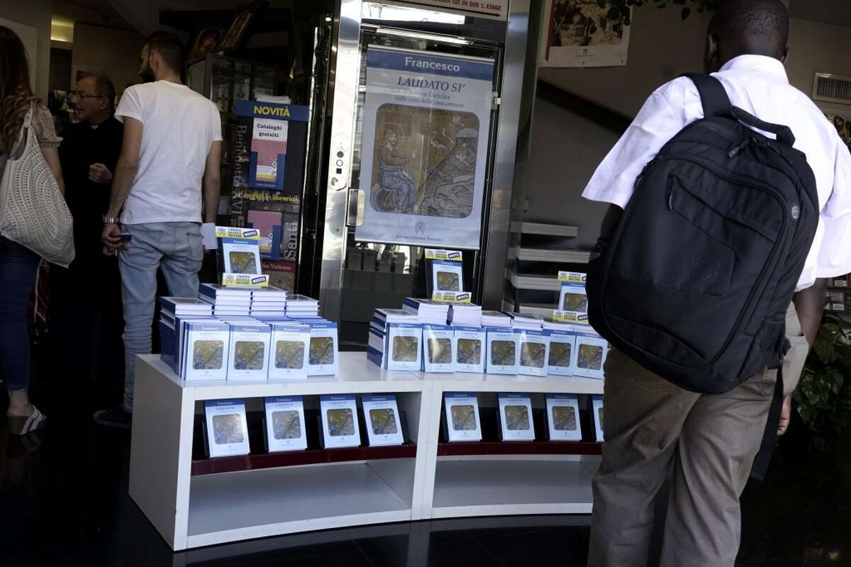 A man looks at copies of Pope Francis' encyclical on sale at the Vatican bookshop, in Rome, Thursday, June 18, 2015. Pope Francis released his much-anticipated encyclical 'Laudato Si' (Praise Be), on the environment Thursday June 18, 2015 declaring an urgent need for the political and spiritual conversion of global leaders and individuals to dedicate themselves to curbing climate change and ending policies and personal habits that destroy creation. (AP Photo/Andrew Medichini)