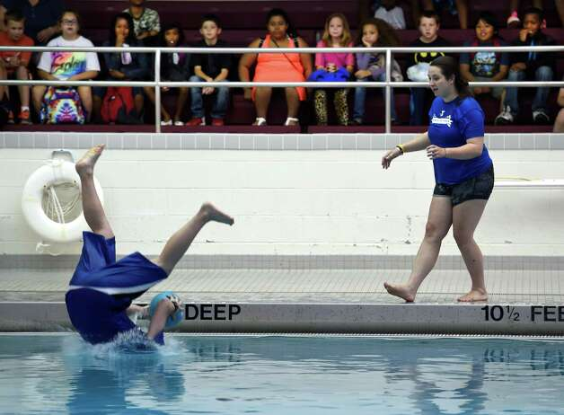 "So. Saratoga Y Head lifeguard Alex Ranucci goes in head first to show fourth graders from Hamilton Elementary School what not to do during the ""Keeping Kids Safe Around Water"" courses Wednesday morning June 17, 2015, at the Schenectady High School pool in Schenectady, N.Y.  Assisting Ranucci is Molly Moran, aquatics director also from Southern Saratoga Y.   (Skip Dickstein/Times Union) Photo: SKIP DICKSTEIN / 00032299A"