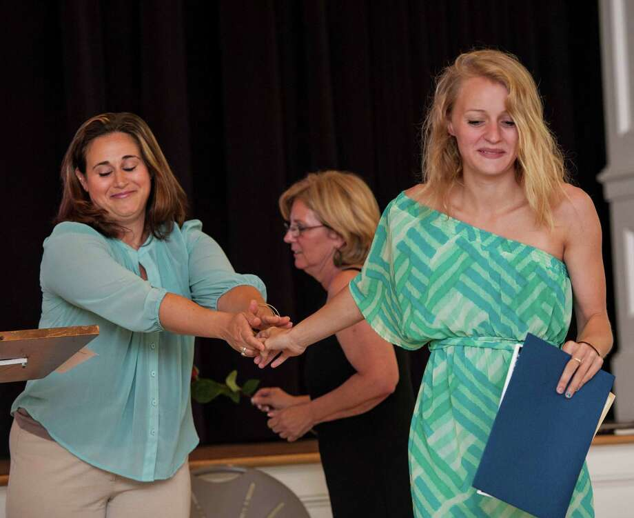 Shelby Curley (right) receives her diploma from teacher Lindsey Pontieri at the Graduation ceremony of the Greenwich Alternative high school held at St Catherine of Siena church in the Riverside section of Greenwich, CT on Thursday, June 18th, 2015. Photo: Mark Conrad, Mark Conrad/For Hearst Connectic / Stamford Advocate Freelance
