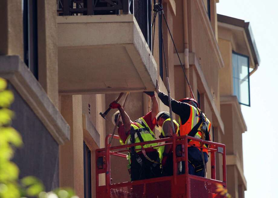 A balcony below the one that collapsed is worked on at 2020 Kittredge Street in Berkeley, California, on Tuesday, June 16, 2015. The collapse, which took place in the early hours of Tuesday, killed 6 and injured others. Photo: Loren Elliott, Loren Elliott / The Chronicle / ONLINE_YES
