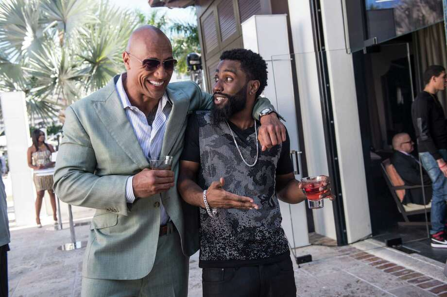 Dwayne Johnson (left) stars as Spencer Strasmore, an ex-NFL player working for a financial management firm, with John David Washington as current player Ricky Jerret.
