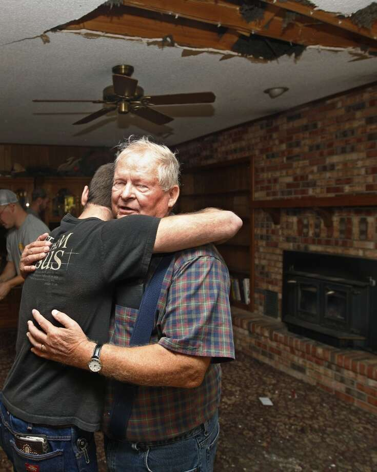 Joe Reneau, right, gets a hug from friend Cody Parsons in his family room in Sparks, Okla. on Sunday, Nov. 6, 2011 after the room was damaged when the chimney collapsed during an earthquake and fell partially through the roof, at upper right. Neither Joe nor his wife were in the room at the time, and were not injured. A team of scientists have determined that a 5.6-magnitude quake in Oklahoma in 2011 was caused when oil drilling waste was injected deep underground. The report was released Tuesday, March 26, 2013 by the journal Geology. That makes it the most powerful quake to be blamed on deep injections of wastewater, although not everyone agrees. Oklahoma's state seismologists say the quake was natural. Photo: Sue Ogrocki, Associated Press