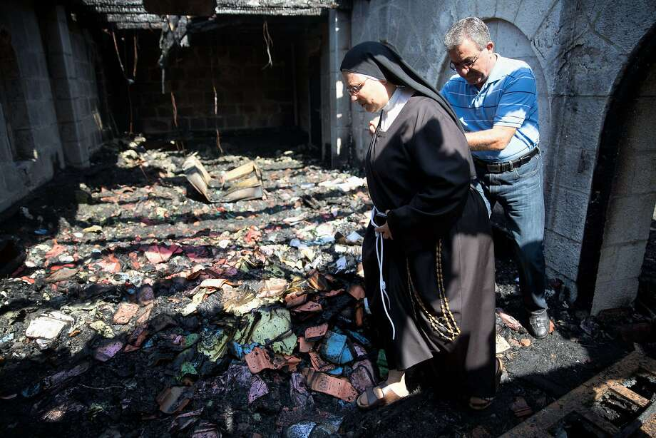 A nun inspects the damage of the Church of the Multiplication on the shores on the Sea of Galilee. Many Christians believe it is the place where Jesus fed the 5,000 in the miracle of the five loaves and two fish. Photo: Menahem Kahana, AFP / Getty Images