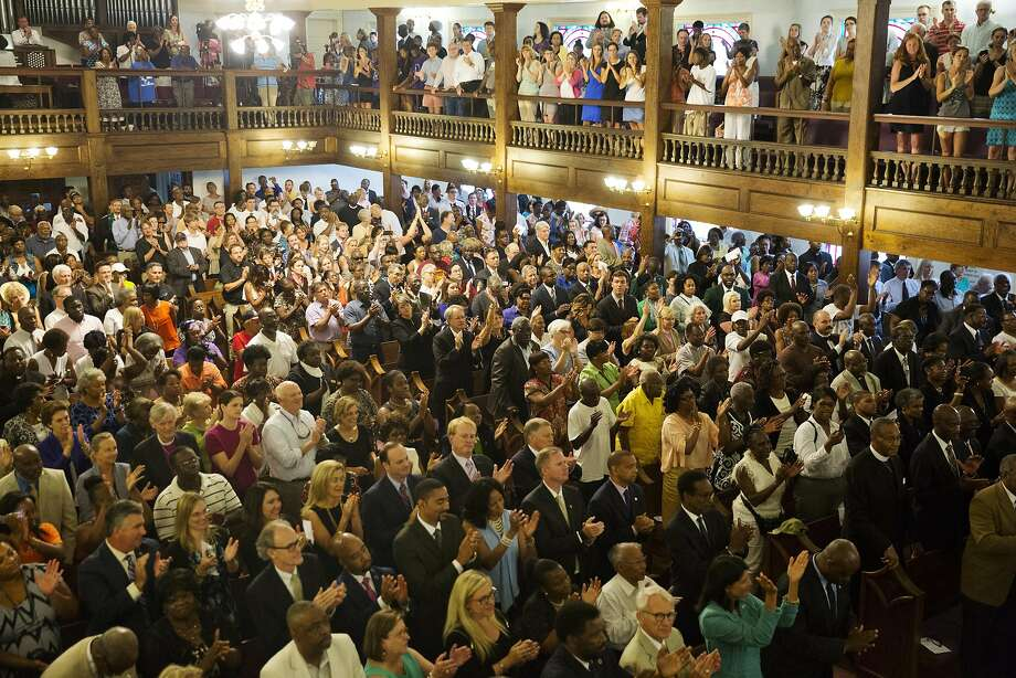Parishioners applaud during a memorial service at Morris Brown AME Church for the people killed Wednesday during a prayer meeting inside a historic black church in Charleston, S.C. Police arrested 21-year-old suspect Dylann Storm Roof Thursday in Shelby, N.C., without resistance. Photo: David Goldman, Associated Press