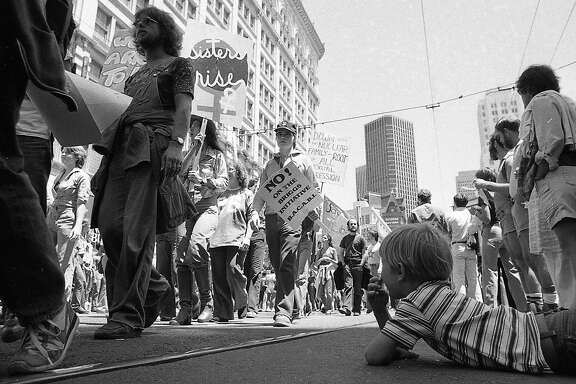 June 25, 1978: A boy watches parade-goers during the 1978 Gay Freedom Day Parade in San Francisco.