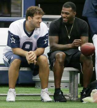 Dallas Cowboys wide receiver Dez Bryant, right, sits on the bench with quarterback Tony Romo (9) during an NFL football minicamp at the team's stadium in Arlington, Texas, in Arlington, Texas, Thursday, June 18, 2015. Bryant joined his teammates for the last day of minicamp. Bryant didn't practice Thursday since he still has not signed his franchise tender that would guarantee him $12.8 million this season. Photo: LM Otero /Associated Press / AP