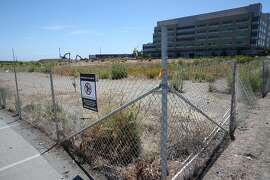 A fence marks the boundary of a parking lot on the Mission Bay site in San Francisco, Calif. on Thursday, June 18, 2015 where the Warriors hope to build a new basketball arena.