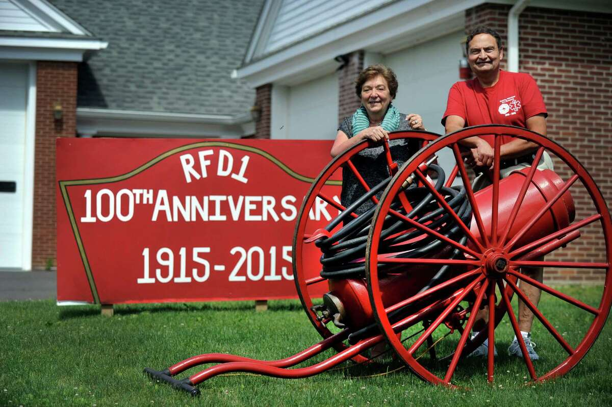 """Patricia Moisio, chairwoman of the centenial committee and Redding tax collector, and Henry Sanford, president of Redding Fire and EMS Co. No. 1 and a fire company lieutenant, with a """"fire extinquisher on wheels."""" It was the first piece of equipment the company purchased in 1915."""